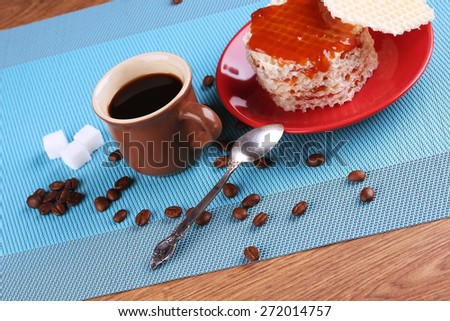 A Cup of coffee on the table. A Cup of espresso. Refined sugar, coffee beans and waffles with jam. Waffles, covered in apricot jam. A delicious dessert. Lunch, snack. - stock photo