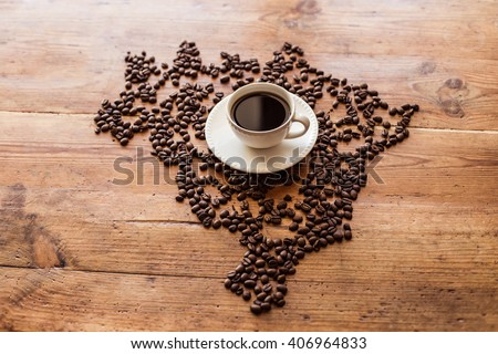 A cup of coffee standing on coffee beans laid out in the shape of Brazil, on a wooden table - stock photo
