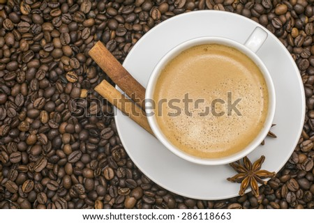 A Cup of coffee with anise and cinnamon and coffee beans - stock photo