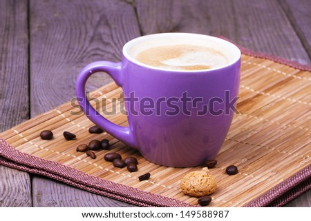 A cup of coffee with coffee beans and amaretti - stock photo