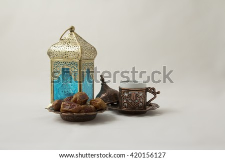 A Cup of coffee with Dates and a Copper Lantern - stock photo