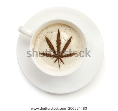 A cup of coffee with foam and powder in the shape of a marijuana leaf.(series) - stock photo