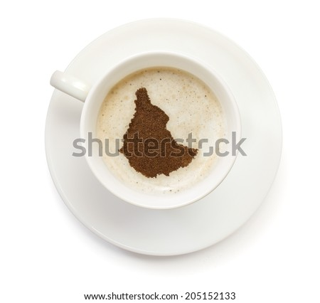 A cup of coffee with foam and powder in the shape of Ethiopia.(series) - stock photo