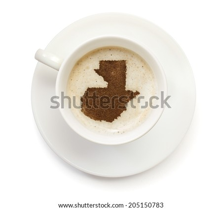 A cup of coffee with foam and powder in the shape of Guatemala.(series) - stock photo
