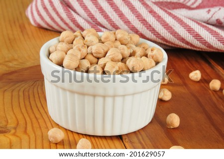 A cup of dried garbanzo beans on a rustic wooden cutting board - stock photo