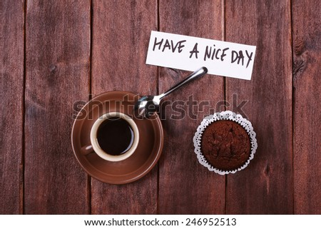 "A cup of espresso, chocolate cake and a note with a wish ""Have a nice day"". A cup of strong black coffee and a snack. Surprise for a loved one - morning coffee. - stock photo"