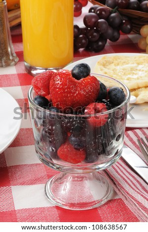 A cup of fresh berries with an english muffin and orange juice for breakfast - stock photo