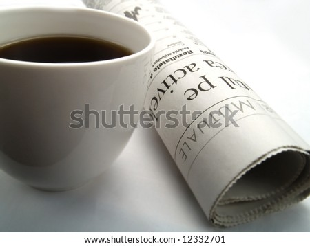 A cup of fresh coffee and a newspaper roll - stock photo