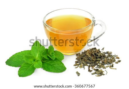 A cup of green tea and a sprig of mint and a handful of uncooked dry green tea isolated on white background. - stock photo