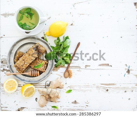 A cup of herbal tea with fresh mint, honey, lemon, ginger on rustic white wooden background. Top view, copy space - stock photo