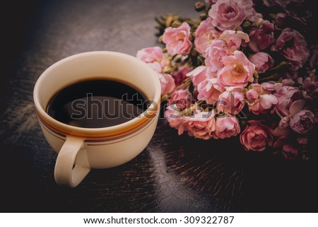 A cup of hot coffee and flowers. Romantic background with retro filter effect - stock photo