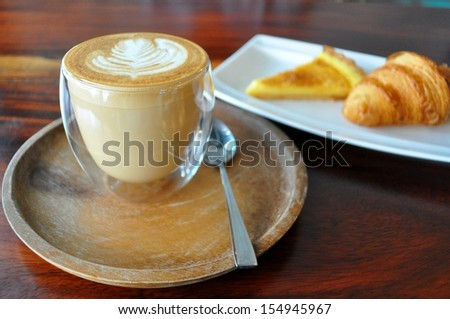A cup of Hot Coffee, Croissant and Passion fruit Tart on wood table in a cafe  - stock photo