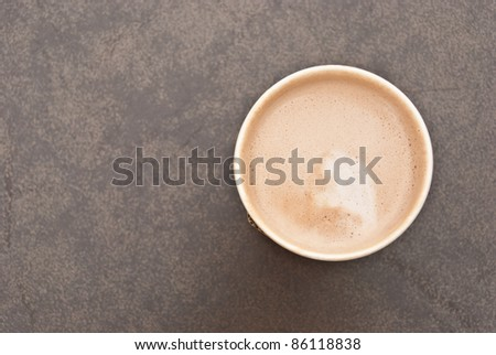 a cup of hot coffee in paper cup taken from the top view with creamy milk inside - stock photo