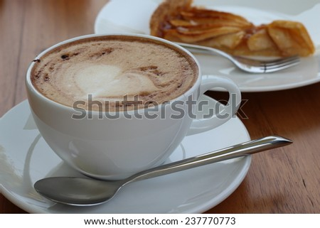 A cup of hot coffee on wooden table - stock photo
