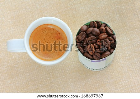 A cup of hot Espresso next to coffee beans wrapped with 100 Euro Banknote - stock photo