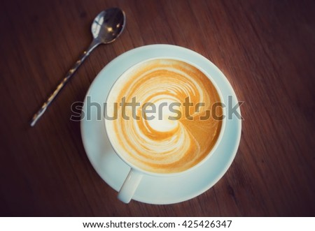 A Cup of hot latte art coffee on wooden table. A cup of hot latte art coffee with heart pattern. hot milk art coffee on wooden table. Vintage latte art coffee. - stock photo