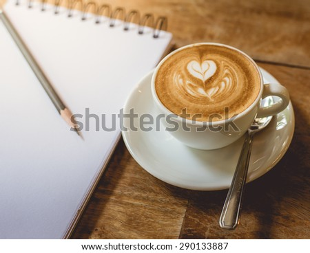 A Cup of hot latte art coffee with papernote and pencil on wooden table vintage tone style - stock photo