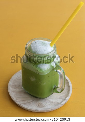 A cup of ice green tea on yellow wood board, drink for health.select focus. - stock photo