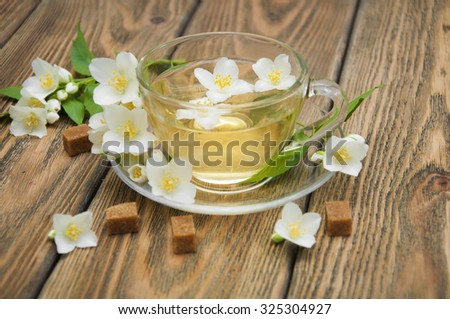 A cup of jasmine tea with jasmine flowers on a wooden background - stock photo