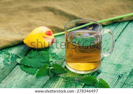 A cup of melissa herbal tea on a wooden table - stock photo