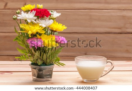 A cup of milk which decorate with flowers by wooden background - stock photo