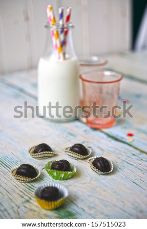 a cup of milk with a straw colored, chocolate sweets on the table - stock photo