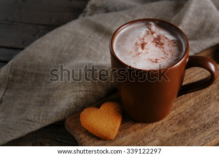 A cup of tasty cocoa on wooden table, close-up - stock photo
