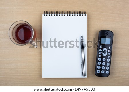 A cup of tea, an open notebook, a fountain pen and a black phone on wooden texture imitating an office desk. - stock photo