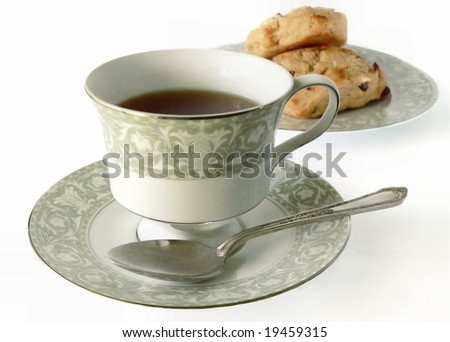 A cup of tea in a decorative china cup and saucer with a spoon resting beside the cup with scones on a matching plate in the background. The china has a green floral design and is trimmed in platinum - stock photo