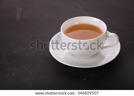 A cup of tea in saucer on top of dark textured table - stock photo