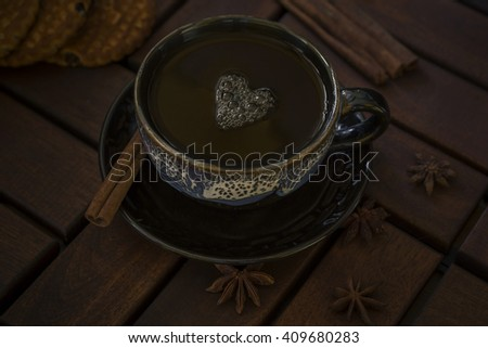 a cup of tea of glazed ceramics. On the saucer cinnamon stick and star anise. Three cookies. - stock photo