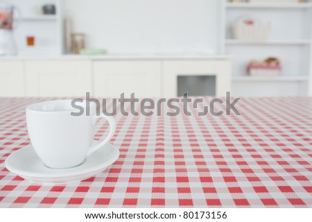 A cup of tea on a tablecloth in a kitchen - stock photo