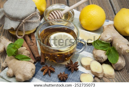 A cup of tea with fresh honey, lemon, ginger and spices on wooden background - stock photo