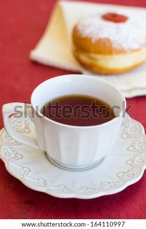 A cup of tea with fresh sufgniya (donut) - stock photo