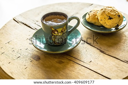 A cup of turkish coffee on the wooden table with cookie - stock photo