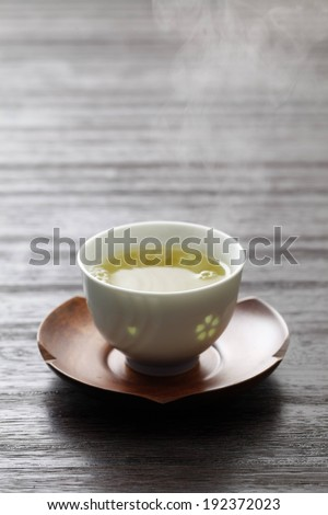 A cup of yellow liquid on a wooden saucer. - stock photo