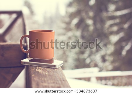A cup with a hot drink  and mobile phone on the background of the winter forest - stock photo