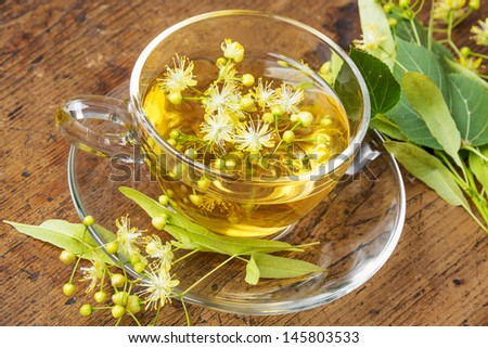 a cup with linden tea on a wooden table - stock photo