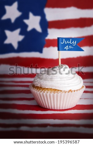 A Cupcake with a July 4th Flag on an American Flag Background - stock photo