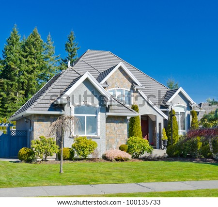 A custom built luxury home in a residential neighborhood. This high end home is very nicely landscaped property. - stock photo