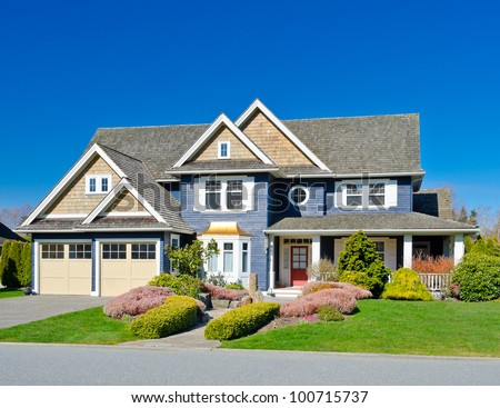 A custom built luxury two garage doors house in a residential neighborhood. North America. - stock photo