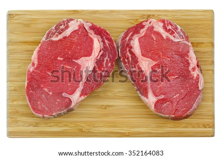 A cut of outer side of the rib : prime Rib Eye steak on a wooden cutting board isolated on a white background  - stock photo