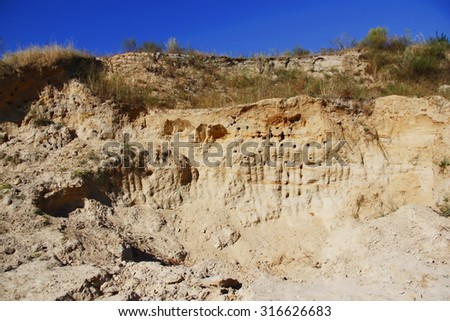 A cut of soil with several layers visible and dried grass on top - stock photo