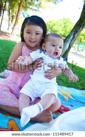 A cute asian girl with boy in the park - stock photo