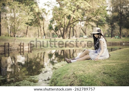 A cute Asian Thai girl is relaxing near the pond in the wilderness in soft vintage color - stock photo