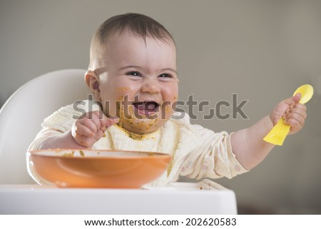 a cute baby girl laughing and raising a spoon during meal time - stock photo