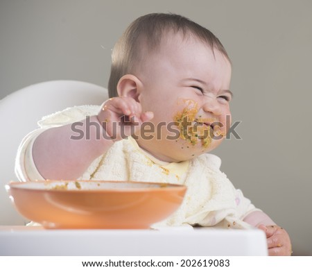 a cute baby girl laughing  during meal time  - stock photo