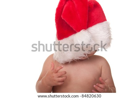A cute baby has a Christmas hat over his head. - stock photo