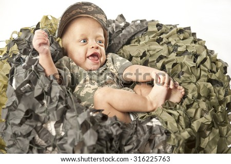 A cute baby sitting in military outfit. - stock photo