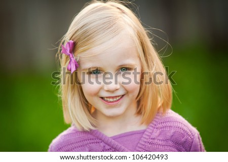A cute blonde little girl is smiling at the camera.  She is wearing a pink sweater. - stock photo